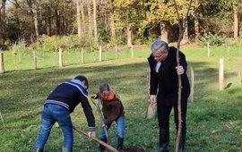 Gedeputeerde ten Bolscher plant met kinderen op landgoed Vilsteren de pronkboom, symbool voor de duizenden bomen die er bij komen.