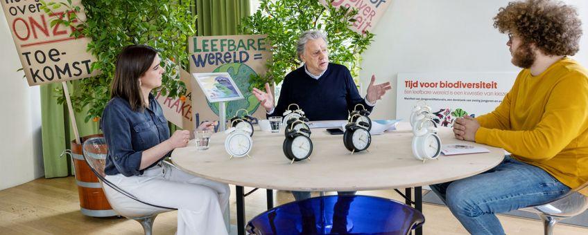 Namens JongerenXNaturalis bieden Aniek Moonen (links) en Auke-Florian Hiemstra (rechts) het manifest aan aan Ed Nijpels (midden.