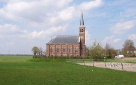 Kerk te Warstiens, Friesland. Op de achtergrond is de oprukkende stad Leeuwarden te zien