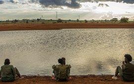 Drie vrouwen zitten bij een waterpoel in Kenia
