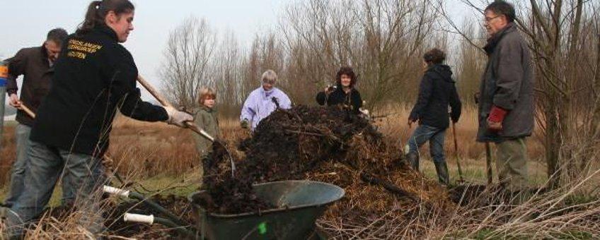 Vrijwilligers leggen een nieuwe broeihoop aan