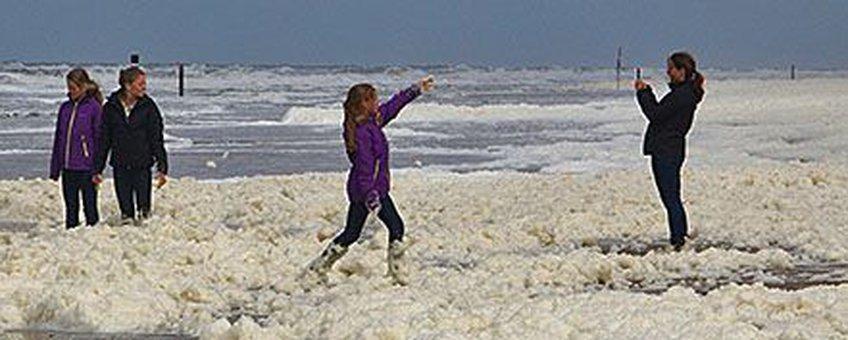 Plezier met schuim op het strand