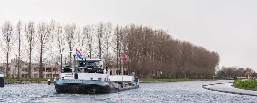 Eerste schip vaart door de bochtafsnijding Delftse Schie; de natuurvriendelijke over in de nieuwe vaargeul is goed te zien